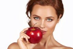 Het jonge mooie sexy meisje met donker krullend haar, naakte schouders en hals, die grote rode appel houden om van de smaak te ge Royalty-vrije Stock Fotografie