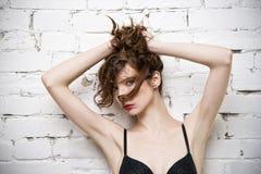 Het jonge mooie sexy vrouw stellen in lingerie dichtbij een witte bakstenen muur Royalty-vrije Stock Foto