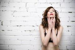Het jonge mooie sexy vrouw stellen in lingerie dichtbij een witte bakstenen muur Royalty-vrije Stock Afbeeldingen