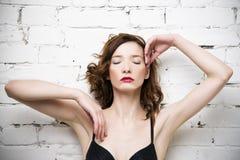 Het jonge mooie sexy vrouw stellen in lingerie dichtbij een witte bakstenen muur Stock Fotografie