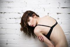 Het jonge mooie sexy vrouw stellen in lingerie dichtbij een witte bakstenen muur Stock Foto