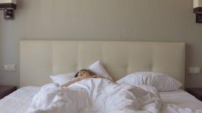 Het jonge mooie slaperige meisje ontwaakte plotseling en zat op het bed stock video