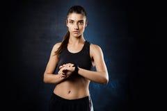 Het jonge mooie sportieve meisje stellen over donkere achtergrond De ruimte van het exemplaar Stock Afbeeldingen