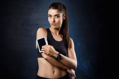 Het jonge mooie sportieve meisje stellen over donkere achtergrond De ruimte van het exemplaar Royalty-vrije Stock Foto