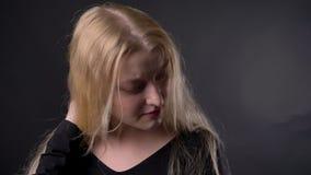 Het jonge mooie vermoeide blonde meisje met roze lippenstift let bij camera, wat betreft haar, op grijze achtergrond stock videobeelden