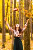Het jonge mooie vrouw geel werpen doorbladert binnen Royalty-vrije Stock Foto's