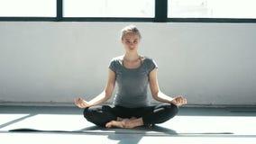 Het jonge mooie vrouw mediteren tijdens binnen opleidingslotusbloem stelt Sportief meisje die yoga op het dak doen Langzame Motie stock video