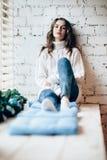 Het jonge mooie vrouw ontspannen op venstervensterbank in Kerstmisdecor Stock Foto