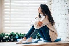 Het jonge mooie vrouw ontspannen op venstervensterbank in Kerstmisdecor Royalty-vrije Stock Foto's