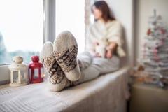 Het jonge mooie vrouw ontspannen op venstervensterbank in Kerstmisdecor Stock Fotografie