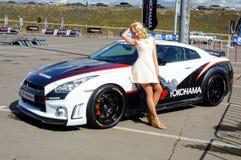Het jonge, mooie vrouw stellen naast Nissan GTR Royalty-vrije Stock Foto