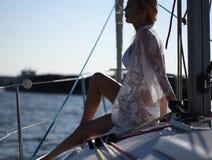 Het jonge mooie vrouwenblonde in bikinis en pareo van het kantstrand zit op het dek van varend jacht stock footage