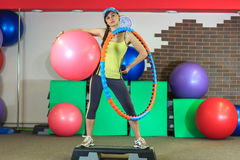 Het jonge mooie witte meisje in gele en grijze sporten past tribunes met een geschikte bal, hoepel en een domoor op het fitness c Royalty-vrije Stock Fotografie