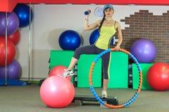 Het jonge mooie witte meisje in gele en grijze sporten past tribunes met een geschikte bal, hoepel en een domoor op het fitness c Stock Afbeeldingen
