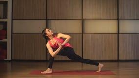 Het jonge mooie yoga stellen stock footage