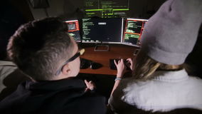 Het jonge multi-etnische het team van computerhakkers binnendringen in een beveiligd computersysteem, die tot een computersysteem stock videobeelden
