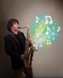 Het jonge musicus spelen op saxofoon terwijl muzieknoten explodin Royalty-vrije Stock Fotografie