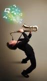Het jonge musicus spelen op saxofoon terwijl muzieknoten explodin Stock Afbeeldingen