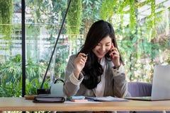 Het jonge onderneemsterwerk met mobiele telefoons en notitieboekjes in royalty-vrije stock afbeelding