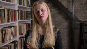 Het jonge ontevreden blonde meisje bevindt zich met haar gekruiste wapens, lettend op bij camera, bibliotheek op achtergrond stock videobeelden