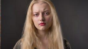 Het jonge ontevreden blonde meisje staart bij camera, grijze achtergrond stock video