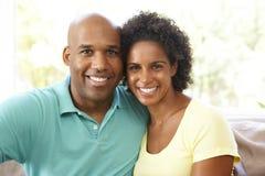 Het jonge Ontspannen van het Paar op Bank thuis Stock Afbeeldingen