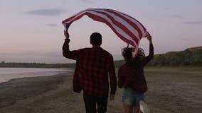 Het jonge paar allebei in rode plaidoverhemden loopt op de kust met Amerikaanse die vlag boven hun hoofden wordt opgeheven achter stock video