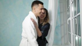 Het jonge paar in badjassen kijkt uit het venster beschouwend als iets, het glimlachen en het kussen grappig stock videobeelden
