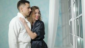 Het jonge paar in badjassen kijkt uit het venster beschouwend als iets, het glimlachen en het kussen grappig stock footage
