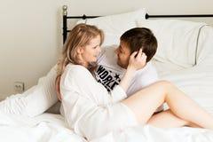 Het jonge paar in bed koestert samen Stock Foto's