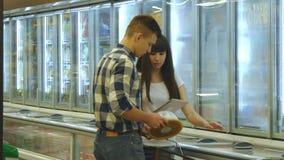 Het jonge paar bevindt zich door de diepvriezer in kruidenierswinkel opslag en het plukken pakketten met bevroren voedsel Mens di stock video