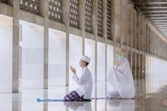 Het jonge paar bidt aan Allah na het doen van Salat stock foto's
