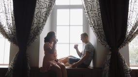 Het jonge paar bij de liefdemens en de vrouw drinken koffie dichtbij venster 1 stock video
