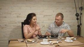 Het jonge paar bij de liefdemens en de vrouw hebben ontbijt thuis 1 stock videobeelden