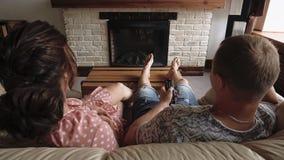 Het jonge paar bij de liefdemens en de vrouw liggen op bank en het letten op TV 1 stock footage