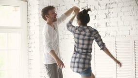 Het jonge paar dansen die zich op comfortabel bed in comfortabele slaapkamer bevinden stock video