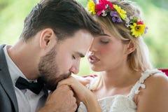 het jonge paar in de Bruid en de bruidegom het kussen van het liefdehuwelijk dient het park in newlyweds Close-upportret van mooi royalty-vrije stock afbeeldingen