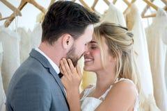het jonge paar in de Bruid en de bruidegom het kussen van het liefdehuwelijk in kleding slaat of winkel op newlyweds Close-upport stock afbeelding