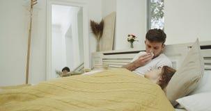 Het jonge paar in de ochtend in bed, mens heeft een griep en het voelen van soozieken stock footage