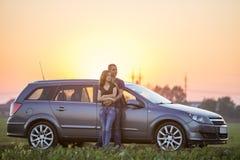 Het jonge paar, de slanke aantrekkelijke langharige vrouw en de knappe man omhelsten samen het leunen bij zilveren auto op groen  stock afbeelding
