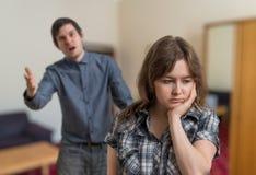 Het jonge paar debatteert De boze man verklaart iets aan droevige vrouw stock fotografie