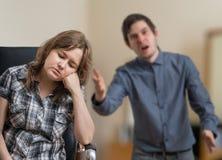 Het jonge paar debatteert De man schreeuwt en verklaart iets aan droevige vrouw royalty-vrije stock fotografie