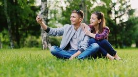 Het jonge paar die in een park rusten, maakt selfie stock video