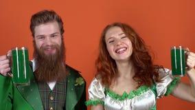 Het jonge paar die in die kostuums de dag van heilige vieren Patrick ` s op oranje muur wordt geïsoleerd juicht groen bier toe stock videobeelden