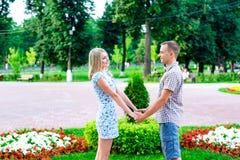 Het jonge paar die zich in de holding van het parklint elkaar bevinden de handen van ` s, een verklaring van liefde, verzacht omh royalty-vrije stock afbeeldingen
