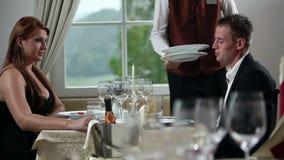 Het jonge paar diner binnen mooi restaurant hebben, en de kelner die brengen stock videobeelden