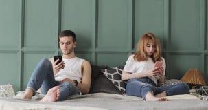 Het jonge paar doorbladert thuis smartphones in hun bed stock videobeelden