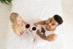 Het jonge Paar drinkt Koffiezitting in Bed, de Gelukkige Glimlach Spaanse Mens en Mening van de Vrouwen de Hoogste Hoek Royalty-vrije Stock Afbeeldingen