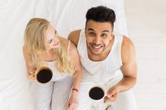 Het jonge Paar drinkt Koffiezitting in Bed, de Gelukkige Glimlach Spaanse Mens en Mening van de Vrouwen de Hoogste Hoek Royalty-vrije Stock Fotografie