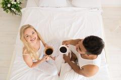 Het jonge Paar drinkt Koffiezitting in Bed, de Gelukkige Glimlach Spaanse Mens en Mening van de Vrouwen de Hoogste Hoek Stock Afbeelding